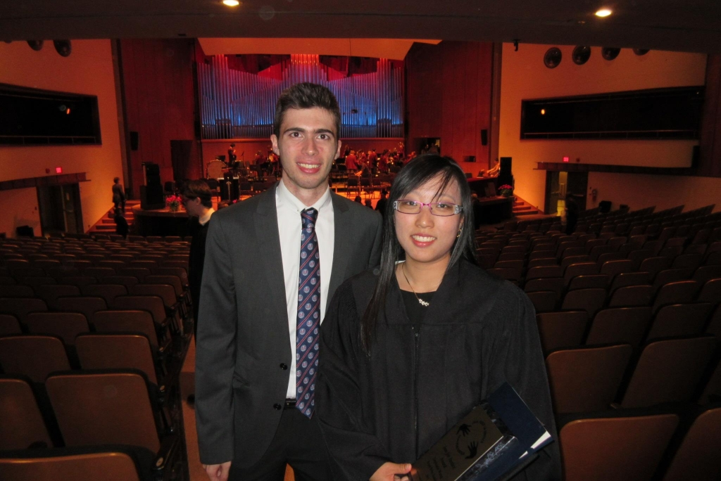 two people smiling in an auditorium