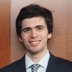 Sean Cohen headshot - Sean wearing a suit standing in front of a wall