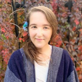 Émilie Gagnier-Marandola headshot - standing in front of a forest with fall colours