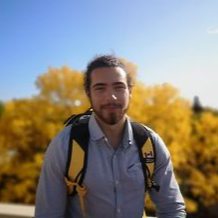 Anthony Kanz headshot - Anthony standing in front of a yellow tree, wearing a yellow backpack
